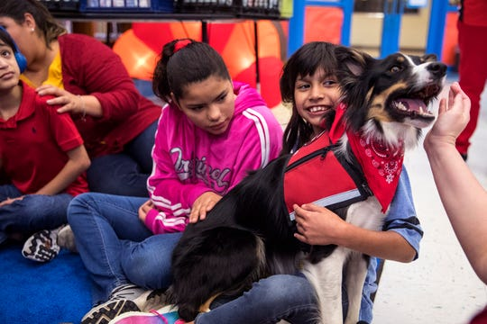 Robstown's Ortiz Intermediate School students Christiana Mungia, center, 11, and Victoria Rojas, 9, interact with therapy dogs from The Go Team on Friday, November 22, 2019.