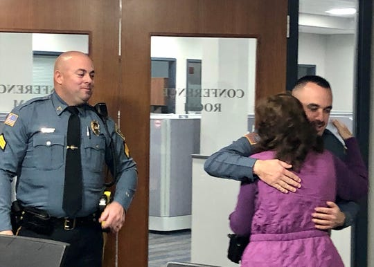 Cynthia Zardus embraces Harrison Township Patrolman Patrick Morris as Sgt. Matthew Neely looks on. The two officers were first on the scene the day Zardus went into cardiac arrest, and saved her with the help of a newly donated defibrillator.