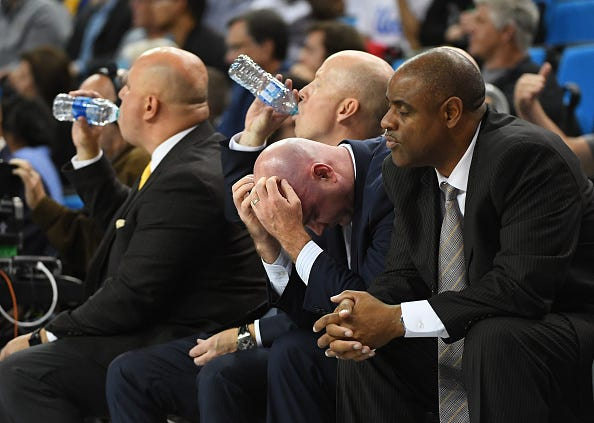 (Left to right) Associate head coach Darren Savino, head coach Mick Cronin, assistant coach Michael Lewis and assistant coach Rod Palmer of the UCLA Bruins sit on the bench during the second half of the game against the Hofstra Pride at Pauley Pavilion on November 21, 2019 in Los Angeles, California.
