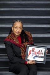 Hope Dudley stands with a poster featuring women who were killed and their cases that remained unsolved in this 2012 photo of the founder of U Can Speak for Me, in Forest Park.