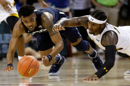 Xavier's Paul Scruggs, left, and Towson's Jakigh Dottin dive for the ball during the first half of an NCAA college basketball game during the Charleston Classic on Thursday, Nov. 21, 2019, in Charleston, S.C.