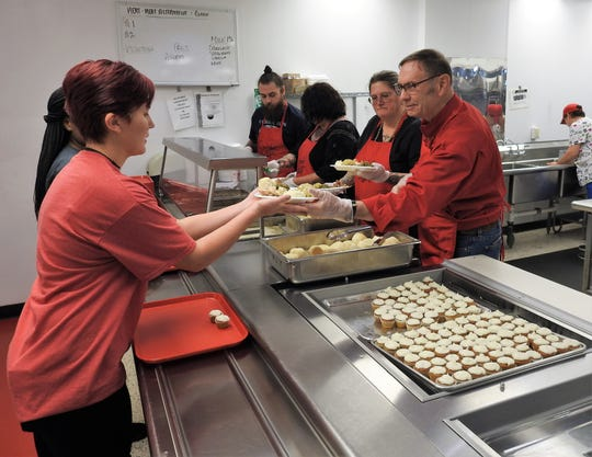 Caitlyn Duling receives a plate from Greg Yurjevic during serving of the 16th annual Community Thanksgiving Dinner at Coshocton High School. Various volunteers from the public work in the kitchen while students from various clubs serve the approximate 600 meals each year.