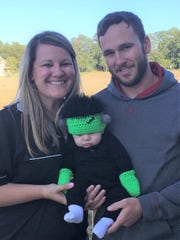 Kelli Hower with her husband Adam and their infant son, who was dressed up for Halloween.