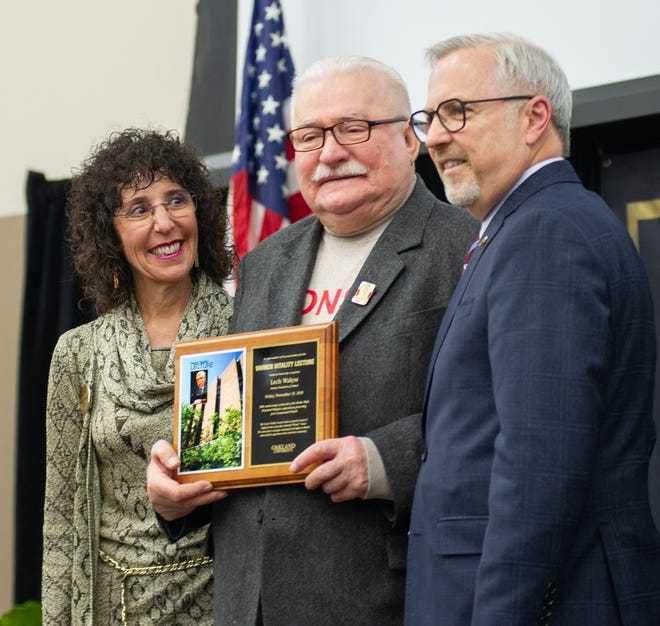 Oakland University President Ora Hirsch Pescovitz and Senior Vice President for Academic Affairs and Provost James Lentini present Lech Walesa, former President of Poland, with the Varner Vitality Series speaker plaque.