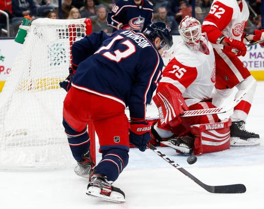 Columbus Blue Jackets forward Cam Atkinson, left, settles the puck in front of Detroit Red Wings goalie Jimmy Howard during the second period of an NHL hockey game in Columbus, Ohio, Thursday, Nov. 21, 2019. Atkinson scored on the play.