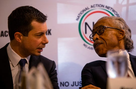 Pete Buttigieg, left, speaks with the Rev. Al Sharpton at a breakfast event on Thursday in Atlanta. Buttigieg, along with Cory Booker, Amy Klobuchar, Andrew Yang and Tom Steyer, all presidential hopefuls, spoke at the event hosted by the Sharpton's National Action Network.