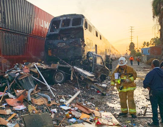 First responders at the scene after an RV was hit by a commuter train and burst into flames along a track in Santa Fe Springs, Calif. on Friday.