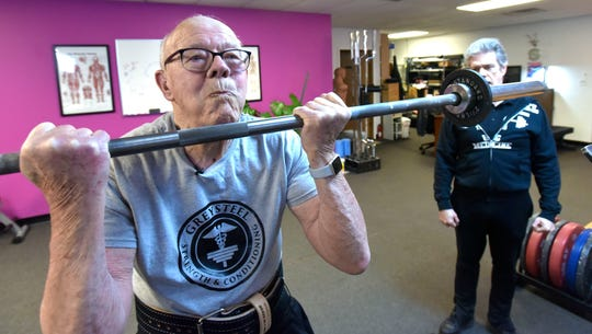 "John Claassen, 93, of Plymouth, does curls under the watchful eyes of Greysteel Strength & Conditioning owner Jonathon ""Sully"" Sullivan at the Farmington Hills  gym."