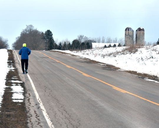 Tony Anderson, 57, runs along Harrand Road south of Traverse City while training for his 48th marathon at the end of the month in Mississippi.