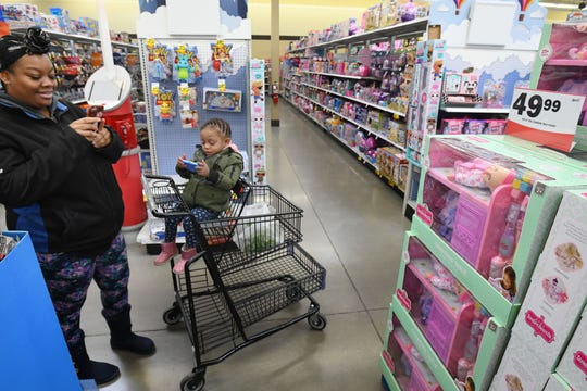 Shavon Samuels sneaks in a photo of a doll she might get for her daughter Lauryn Hill, 2 who at the moment was more interested in the phone instead of her potential presents.  Shopping and shoppers at Meijer on 8 mile in Detroit on Nov. 22, 2019.