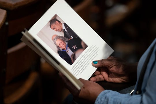A person looks through the program before the start of the Celebration of the Life of Toni Morrison.