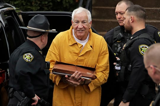 Former Penn State University assistant football coach Jerry Sandusky, center, arrives at the Centre County Courthouse for resentencing on his 45-count child sexual abuse conviction Friday.