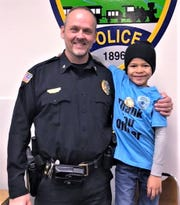 Dakota Rinker poses with Elmira Heights Police Chief Rick Churches after dropping off gift bags for police officers.