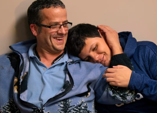 Richard Colacecchi and Daniel, 14, wait their turns for a hair cut at The Hair Factory in Evansville a week ago Friday.