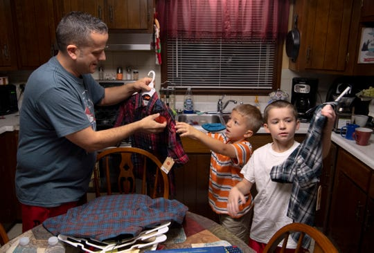 """Eli, 6, and Zander, 8, receive their new plaid shirts from soon-to-be dad, Richard Colacecchi, about two hours before their official adoption at the Civic Center Thursday morning. All four brothers looked """"fresh"""" in their new shirts, trousers and shoes."""