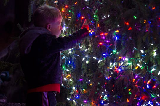 Vaughn DeYoung, 3, plays with the lights on the 36-foot-tall, 30-foot-wide Norway Spruce in front of the Civic Center Thursday evening, Nov. 21, 2019.