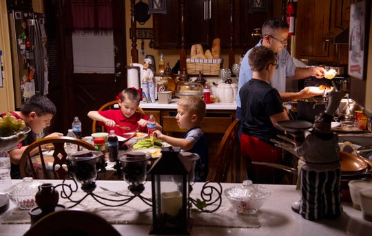 Richard Colacecchi dishes up a hot meal of chicken, sweet corn, noodles and mashed potatoes for his soon-to-be adopted boys at their Evansville home a week ago Friday. Colacecchi said one of his main duties was making sure his boys had a hot meal every night.