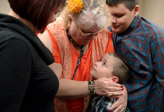 Sharon Beccia, center, congratulates two of her four new grandsons, Zander, 8, center, and Daniel, 14, after their adoptions during National Adoption Day at the Civic Center Thursday morning.