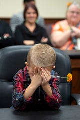 Eli Colacecchi, 6, has a moment of bashfulness after the lawyer asks him what his new name will be after his adoption by new dad, Richard Colacecchi, on National Adoption Day at the Vanderburgh County Thursday morning.
