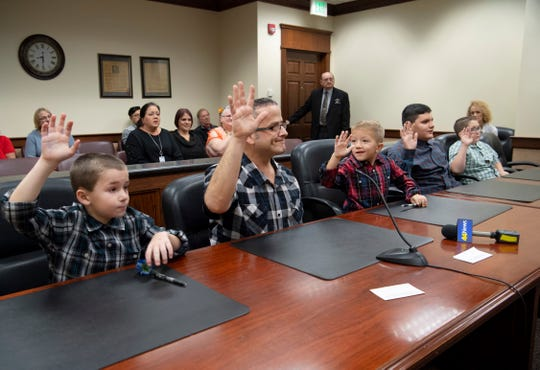 The Colacecchi men raise their right hands as their adoption ceremony begins in a Civic Center courtroom Thursday morning. Richard Colacecchi was adopting the four boys he has been fostering, from left, Zander, 8, Eli, 6, Daniel, 14, and J.T., 13.