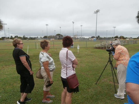 Nature of Cape Coral Bus Tour participants look at a burrowing owl in a protected area through a spotting scope  set up by event host Cheryl Anderson of Cape Coral Friends of Wildlife at the Pelican Baseball Complex.