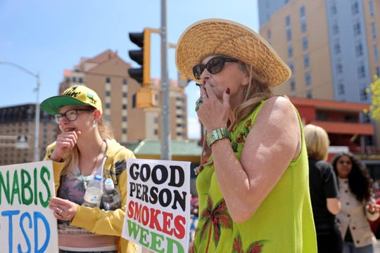 "Liisa Kemp, 60, smokes a joint as supporters gather for a pro-marijuana legalization march in Madison, Wis., on May 4, 2019. ""I've been smoking pot since 1976,"" Kemp says, adding that she has always worked full-time, has traveled the country and owns a house. At left, Caysie Dolan, 22, says she smokes marijuana to help with her post-traumatic stress disorder from a 2012 car accident. She says she has tried 13 pharmaceuticals and none has worked as well as marijuana. While some Wisconsin residents use marijuana illegally as medicine, physicians caution some people should avoid it, including adolescents, pregnant women and individuals with a history of mental illness."