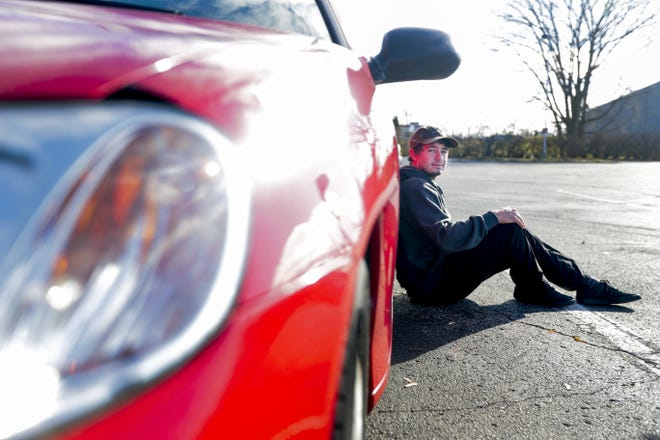 "Caullen Matthew Omdahl poses for a portrait with first hybrid purchase which also happens to be the first hybrid ever sold in America, a 2000 Honda Insight Hybrid. ""A fun fact about this car is it is a manual speed,"" Omdahl said.  Ebony Cox/USA TODAY NETWORK-Wisconsin"