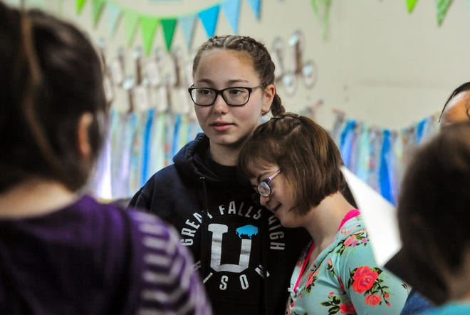 Nicole Hilbig, left, an eighth-grader at East Middle School hangs out with classmate Kelsey Gaskell in Mary Beth Tolan's life skills class at East Middle School. In addition to volunteering as an aide in the life skills class, Hilbig is also raising money for the Great Falls Polar Plunge, a fundraiser for Montana Special Olympics.