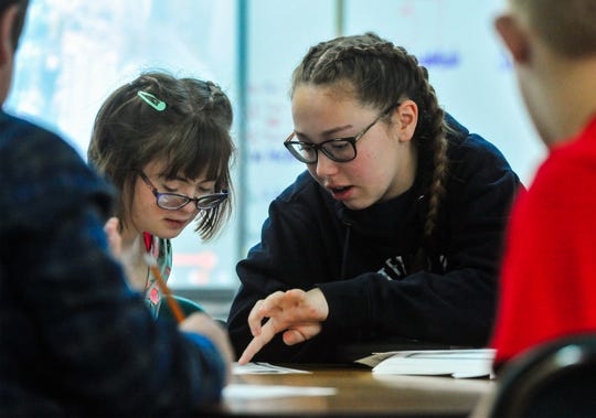 Nicole Hilbig, right, an 8th grader at East Middle School does a word puzzle with fellow 8th grader Kelsey Gaskell in Mary Beth Tolan's life skills class at East Middle School.  In addition to volunteering as aid in the life skills class she is also raising money for the Great Falls Polar Plunge, a fundraiser for Montana Special Olympics.