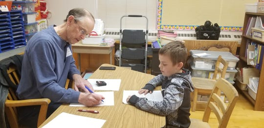 RSVP volunteer Brian Hopkins tests second grade students' reading skills. Here he works with Sonny Wynn at Lewis and Clark Elementary.