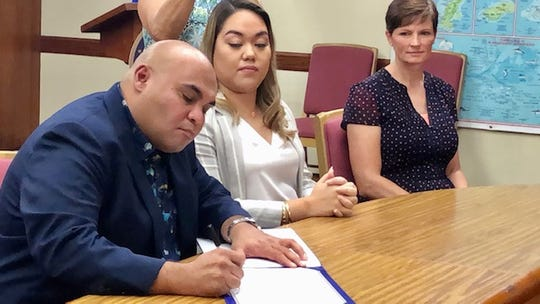 Acting Gov. Josh Tenorio signs on Nov. 22, 2019 a proclamation declaring Nov. 23 as National Adoption Day and November as National Adoption Month, while Sen. Amanda Shelton and Ohala' Adoptions director Traci Anderson look on.