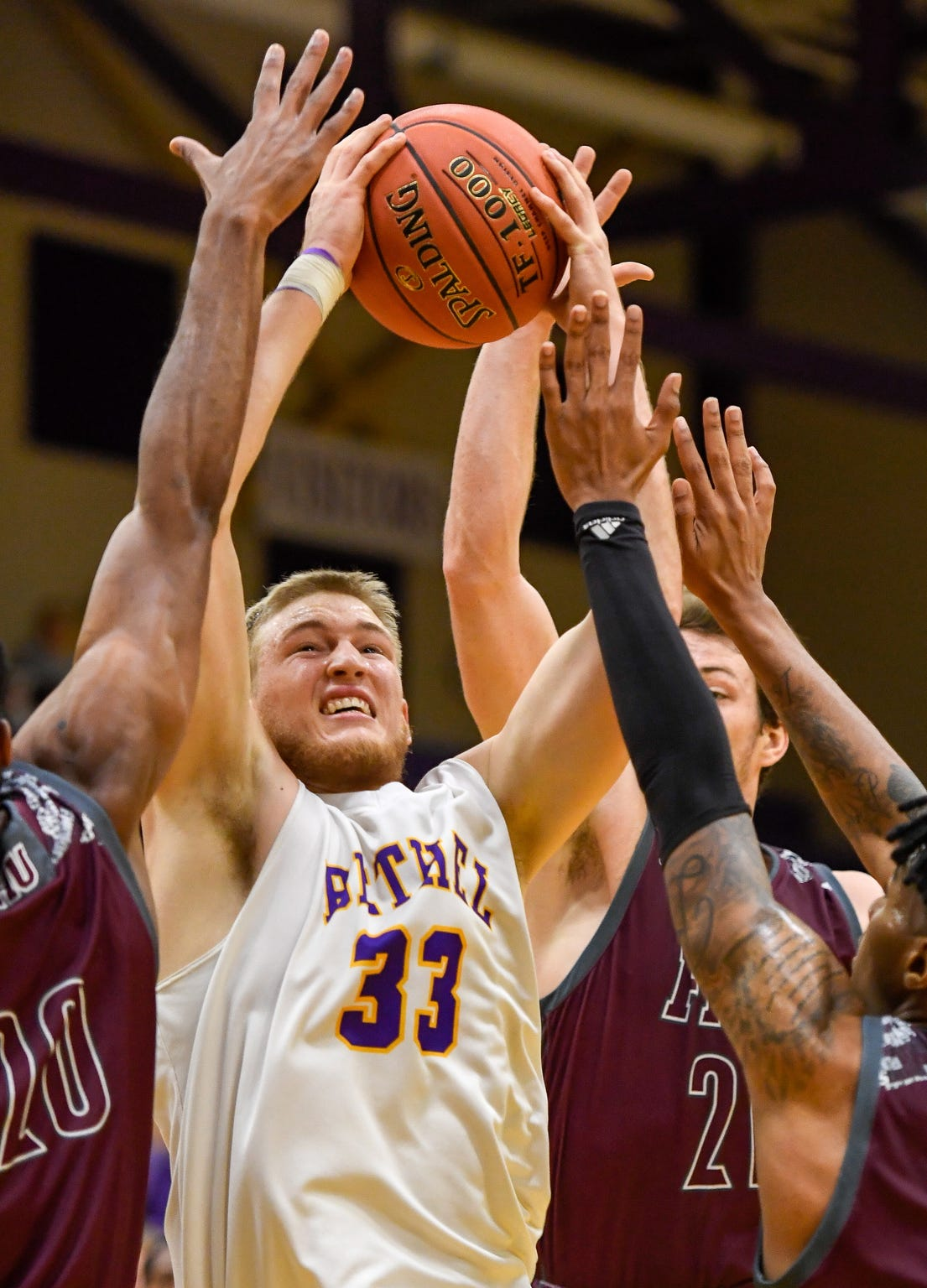 Surrounded by Freed-Hardeman defenders, center, Cayden Edmonson, with the Bethel Wildcats, takes the ball to the basket during a game at Bethel's Crisp Arena Thursday evening, November 14, 2019
