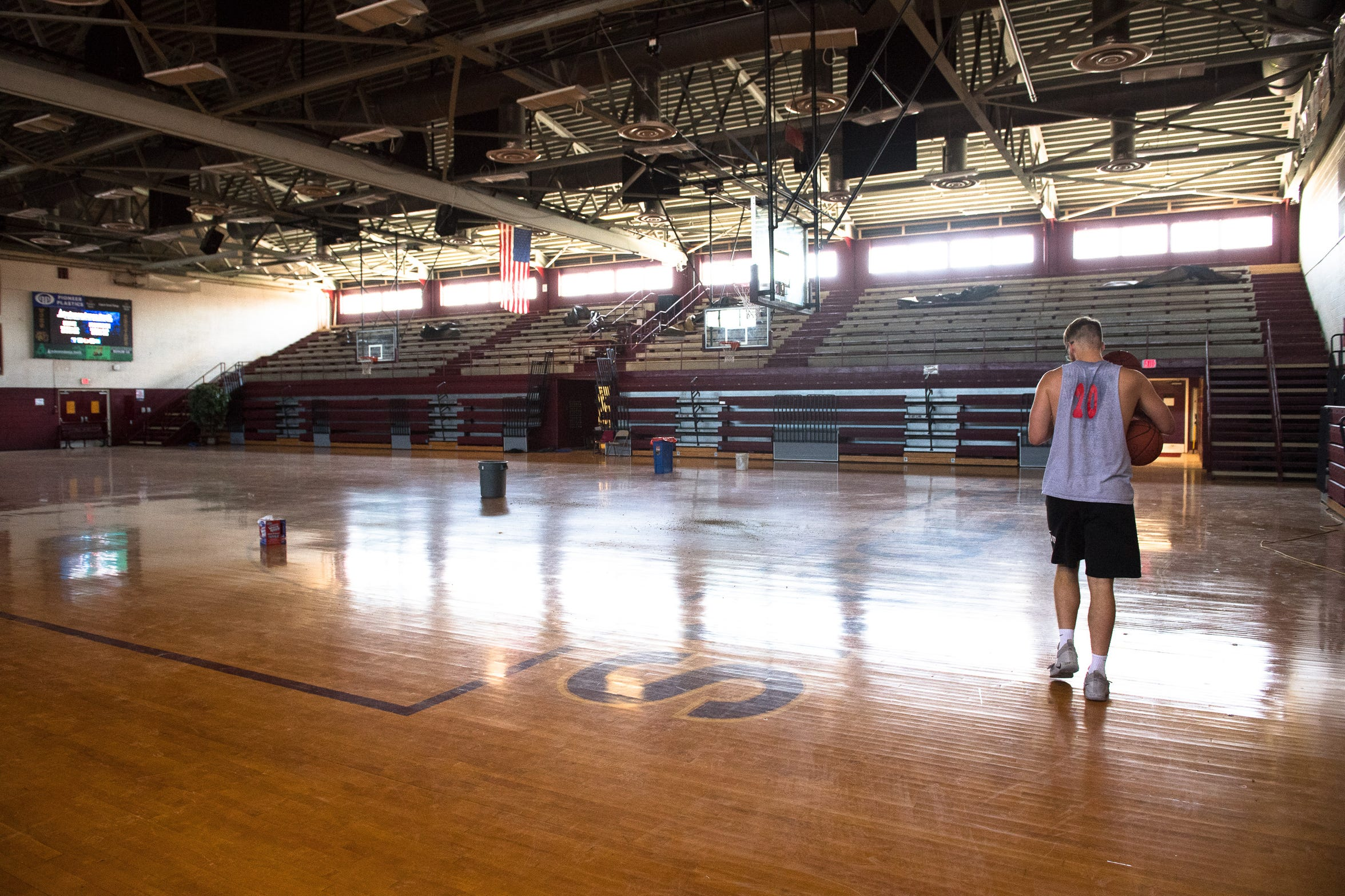 Bethel University senior Cayden Edmonson walks through an empty Webster County High basketball gym on his way to a lone workout with an automatic rebounding machine Monday, July 25, 2019.