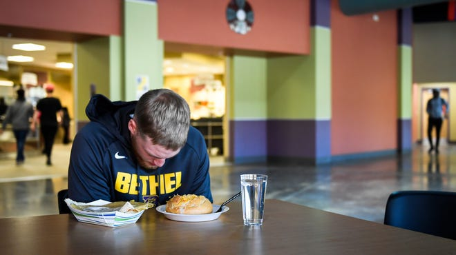 With spirituality an important part of his life, Bethel University senior, Cayden Edmonson takes a moment for prayer before breakfast at the start of a game day on campus Thursday, November 14, 2019.