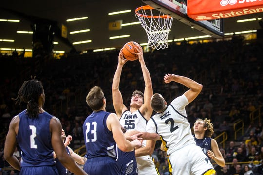 Iowa center Luka Garza (55) grabs a ball up at the rim for a put-back during a NCAA non-conference men's basketball game, Thursday, Nov. 21, 2019, at Carver-Hawkeye Arena in Iowa City, Iowa.