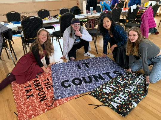 From left, Evelyn Van Ness, Sydney Lilly and Ella Mann, art students at Charles O. Dickerson  High School in Trumansburg, were among participants at a protest banner workshop last week at the Trumansburg Conservatory of Fine Arts.