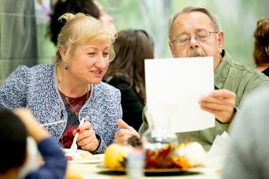 Svitlana Hutvert, of the Ukraine, and Dwight Goodman, of LaFollete, look at a card together while eating dinner at Knoxville International Network's first Community Thanksgiving Potluck at Powell Elementary School in Powell, Tenn. on Thursday, Nov. 21, 2019. The faith-based Christian non-profit works to welcome people from other countries.