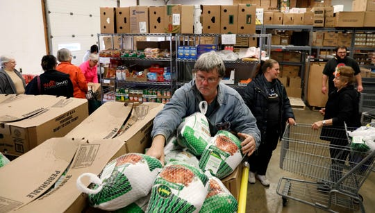 Lutheran Social Service's volunteer Chuck Vickroy grabs a frozen turkey Friday, Nov. 22, 2019, at the agency's food pantry in Lancaster. LSS gave away Thanksgiving meals to about 450 families.