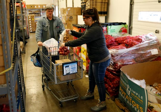 Stacey Sams puts potatoes and onions into a shopping cart that fellow volunteer Chuck Vickroy is taking through the line Friday, Nov. 22, 2019, for a Lutheran Social Services client in Lancaster. LSS gave away Thanksgiving meals to about 450 families.