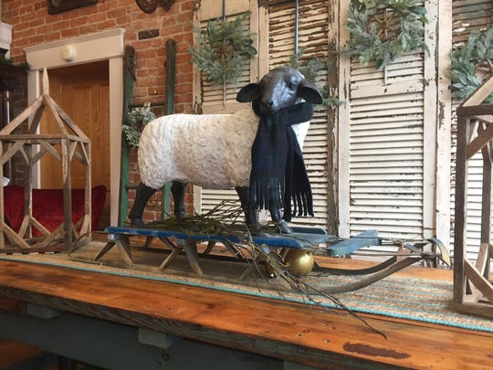 A sheep statue on a vintage sled is seen at Howell shop Like Mother Like Daughter Vintage Treasures, Friday, Nov. 22, 2019.