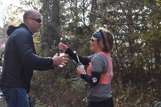 Jeff Hickman gives Loretta Tobolske-Horn, of Brighton, a drink while Tobolske-Horn runs in the Tunnel Hill 100 race on Nov. 9, 2019, at the Tunnel Hill State Park in Vienna, Illinois. Hickman was part of Tobolsky-Horn's team during the race.