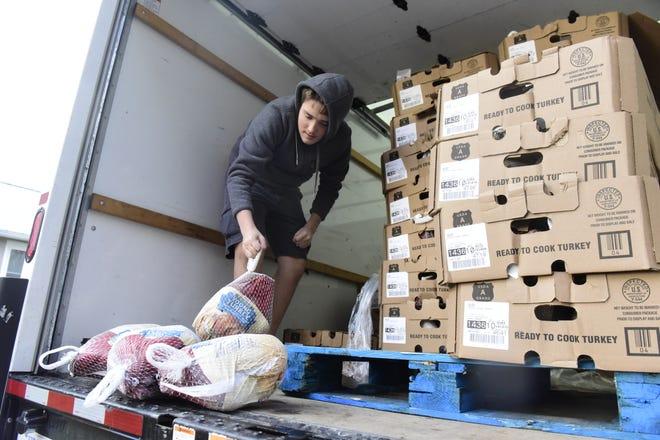 Jonathan Fahey, a junior from Lexington High School, helps unload frozen turkeys Friday at Rinehardt Law Office.