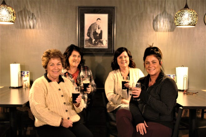 Meg Knickel, second from left, owns and operates O'Dea's Pub along with her husband, Rodney Knickel. The pub is located inside Cooper's Bowl, the family's bowling center at 191 Barks Road West, Marion. Meg is shown with, from left, her mother, Mary (O'Dea) Weston, and her sisters, Julie Atkinson and Katie Benson. A photo of Mary's father, Roger Vincent, hangs on the wall behind them.