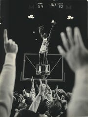 """Marquette player Michael Wilson celebrates on top of the rim at the MECCA after MU beat Notre Dame, 54-52, in 1981 on a last-second shot from Glenn """"Doc"""" Rivers."""