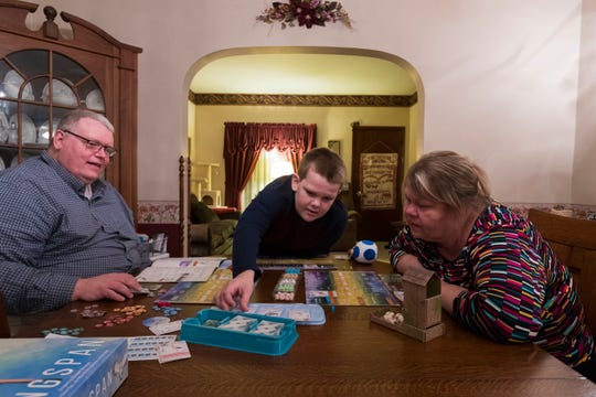 Jack Anderson, center, plays a game with his parents, Darrin and Sarah at their home in Oshkosh. Jack and his late older brother, Henry, were born with a disorder called Bruton's X-linked agammaglobulinemia (XLA).
