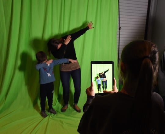 Mountain Home seventh-grader Hannah Baker takes a photo of a dabbing Tucker Coleman and Leah Coleman in front of a green screen Tuesday night at the EAST Night Out event on the campus of Arkansas State University-Mountain Home. EAST students swapped out the green background with a moonscape before printing the photo for the Colemans.