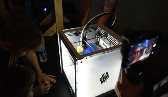 A 3D printer builds a clamp for a J-hook Tuesday night at the EAST Night Out event in the Vada Shied Community Development Center.