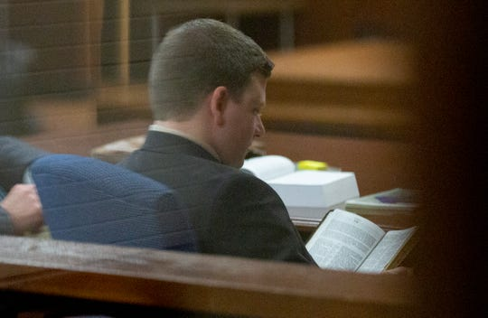 Montgomery police officer A.C. Smith reads his Bible inside the courtroom while a jury decides his fate.