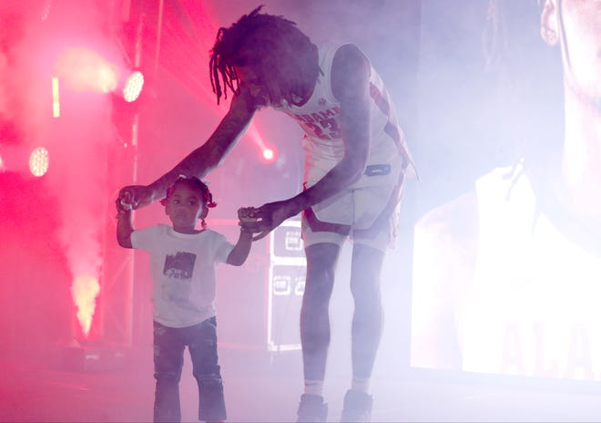 Alabama junior wing John Petty Jr. (23) walks his daughter, Aubrielle, through a fog-filled stage after being introduced prior to the annual Tide TipOff event Oct. 18, 2019 inside Coleman Coliseum in Tuscaloosa, Ala. (Photo by Robert Sutton/Alabama athletics)
