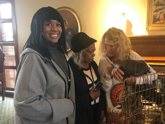 Alma McLemore, Mary Hunter and Laura Turner interact with Beautiful the turkey at a Thanksgiving celebration at St. Paul's Episcopal Church attended by the Spring Street Seniors group.